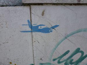 kleines Flugzeug in Blau an getaggter Wand - Detail