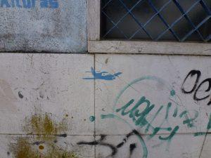 kleines Flugzeug in Blau an getaggter Wand