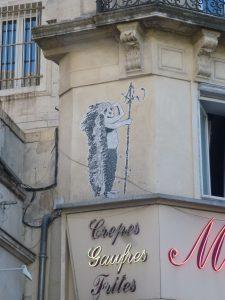 Street Art: PasteUp: Kleiner Indianer mit großer Federpracht an der Mauer von Montpellier