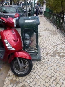 versteckt hinter einem Roller an einer Mülltonne - Lissabon / Portugal
